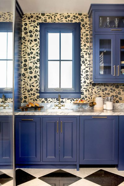 bathroom design with blue cabinets and wallpaper